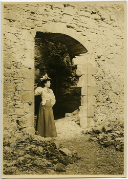 Anna McQueston Johnson standing under an arched entryway in the ruins of Logie House in Scotland