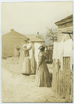 Two black women hanging laundry on a fence in Tuskegee, Alabama