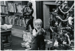 Kid and Christmas tree in the kids room at the Jones Library