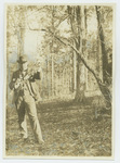 Booker T. Washington examines a tree branch